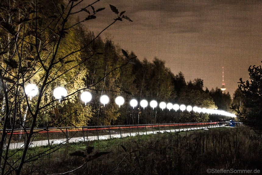 "Along the former Berlin Wall - now the edge of a small birch forest - the illuminated balloons form the ""25 years Fall of the Wall"" installation."